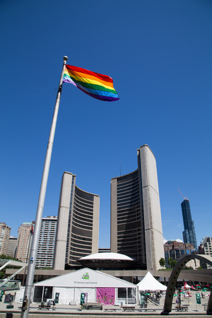 TORONTO, CANADA - 22ND JUNE 2014: World Pride Flag in Toronto with City Hall in the background