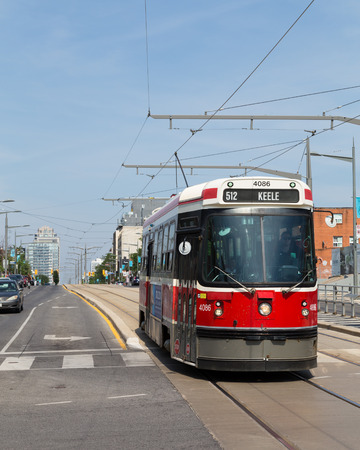 clair: TORONTO, CANADA - 28TH JUNE 2014: A street car on the tracks on St Clair West Road during the day
