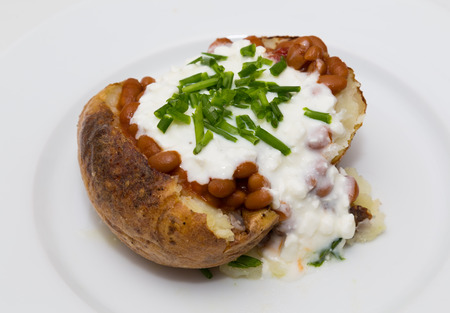 potatoe: Closeup to a baked potatoe with baked beans, cottage cheese and chives on it Stock Photo