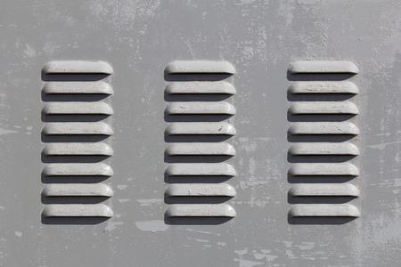 slits: Closeup to a gray heating vent