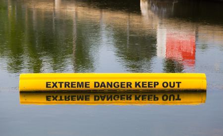 visibility: A closeup to a sign which is warning of extreme danger in the water