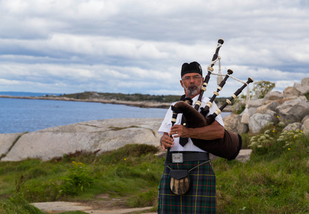 bagpipes: PEGGYS COVE, CANADA - 23RD AUGUST 2014: A man outside playing the Bagpipes during the day in Peggys Cove