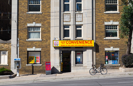 convenience store: TORONTO, CANADA - 3RD SEPTEMBER 2014: The outside of a convenience store in midtown Toronto during the day showing a Bell telephone terminal and Post Box outside Editorial