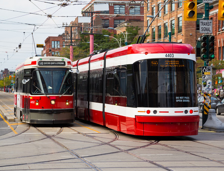 september 9th: TORONTO, CANADA - 9TH SEPTEMBER 2014: An old and new Streetcar alongside each other along Spadina Avenue Editorial