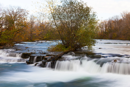 Fast flowing stream with a tree on an island photo