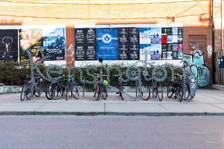 kensington: TORONTO, CANADA - 2ND NOVEMBER 2014: A sign for Kensington in Toronto. Bikes can be seen attached to it.