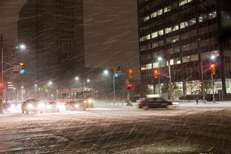 TORONTO, CANADA - 19TH NOVEMBER 2014: A snowstorm in Toronto at night, showing a Street Car and Traffic on the road