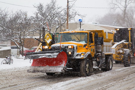 grit: TORONTO, CANADA - 11TH DECEMBER 2014: Large truck in Toronto with a snowplow fitted and holding grit in the rear