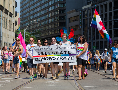 dyke: TORONTO, CANADA - 28TH JUNE 2014: People Celebrating for the Annual Dyke March in Central Toronto holding a University of Toronto, Celebrate, Demonstrate banner Editorial