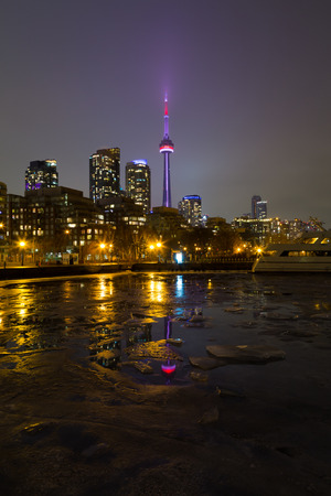 building cn tower: TORONTO, CANADA - 18TH JANUARY 2015: The CN Tower and buildings in the winter, showing Ice in the foreground