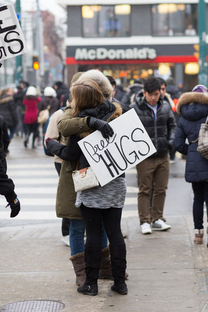 somebody: TORONTO, CANADA - 24TH JANUARY 2015: Somebody holding a Free Hugs sign in Toronto and hugging somebody