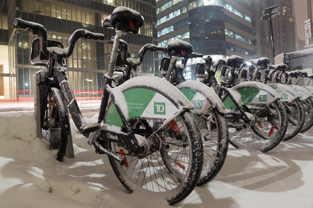 td: TORONTO, CANADA - 7TH FEBRUARY 2015: Toronto Bike Share bikes in at night with snow on them