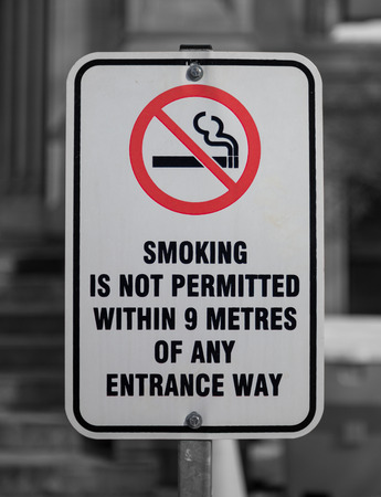 permitted: A Smoking is not permitted within 9 metres of any entrance way sign. Stock Photo