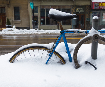 burried: TORONTO, CANADA - 22ND FEBRUARY 2015: A bike and bike lock in Toronto during the winter, showing lots of snow