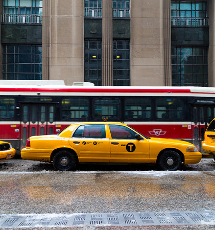 streetcar: TORONTO, CANADA - 22ND FEBRUARY 2015: A New York City Taxi in downtown Toronto during the day. A Streetcar can be seen behind it Editorial