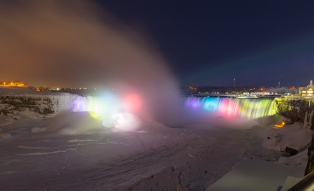 horseshoe falls: NIAGARA FALLS, CANADA - 25TH FEBRUARY 2015: The Horseshoe Falls at night in the winter, showing lightbeams on the Falls and snow and ice
