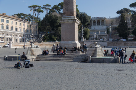 busker: ROME, ITALY - 12TH MARCH 2015: People at the Piazza del Popolo in central Rome. A busker can be seen sitting in front of people with an instrument