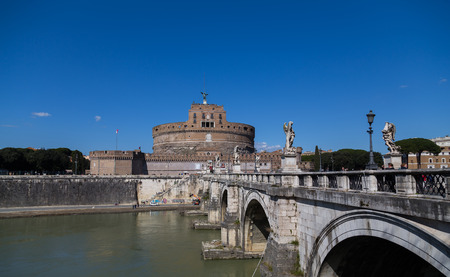 pons: ROME, ITALY - 12TH MARCH 2015: Castel SantAngelo (Castle of the Holy Angel) and the Ponte SantAngelo bridge from the side. People can be seen around the building and on the bridge