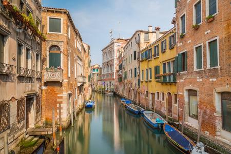buildings on water: Calles de Venecia durante el d�a que muestran viejo colorido edificios, el agua y los barcos Foto de archivo