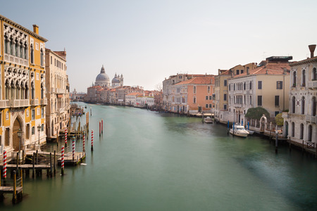 A view of colourful buildings along the Grand Canal in Venice. Basilica di Santa Maria della Salute can be seen in the distance photo
