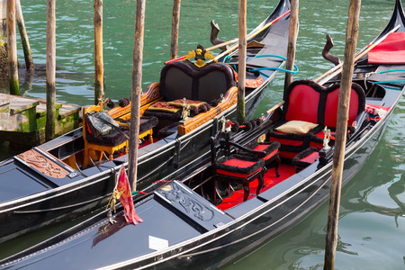 waterside: VENICE, ITALY - 15TH MARCH 2015: Typical Gondolas docked at the waterside in Venice.