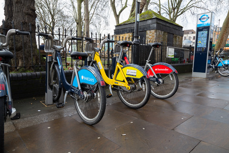 boris: LONDON, UK - 26TH MARCH 2015:  Different coloured hire bikes docked in London. The blue is for Barclays, Yellow for Tour de France and Red for Santander.