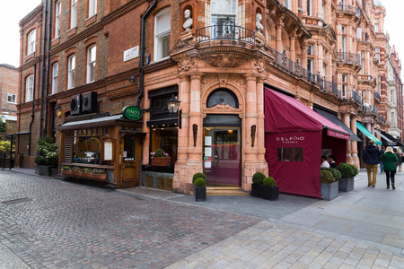 uk cuisine: LONDON, UK - 27TH MARCH 2015:  The outside of Delfino Pizzeria Restaurant in Mayfair London during the day. People can be seen on the restaurant Patio