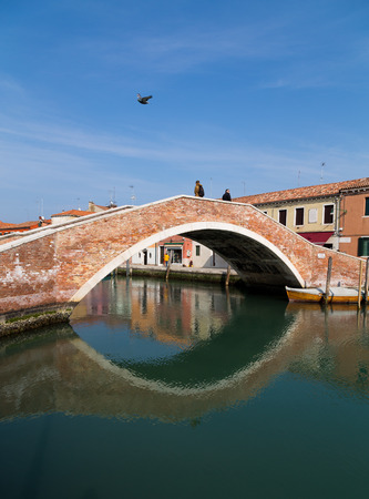 Murano: MURANO, ITALY - 14TH MARCH 2015: An old Bridge in Murano, Italy. People can be seen on the bridge and by buildings.