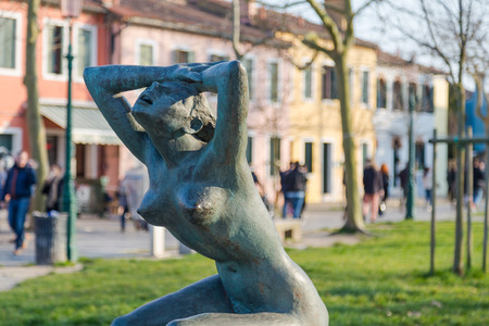 pace: BURANO, ITALY - 14TH MARCH 2015: La Tua Pace statue near Burano port. Large amounts of people can be seen in the distant
