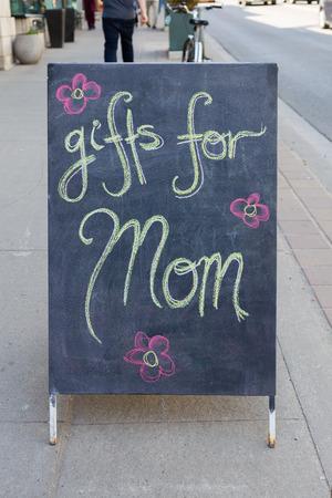 atraer: A regalos para mam� sesi�n fuera de una tienda durante el d�a para atraer a la gente a la tienda para comprar regalos