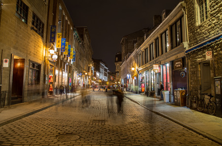 rue: MONTREAL, CANADA - 17TH MAY 2015: Buildings and businesses along Rue Saint Paul in Old Town Montreal at Night. The blur of people can be seen. Editorial