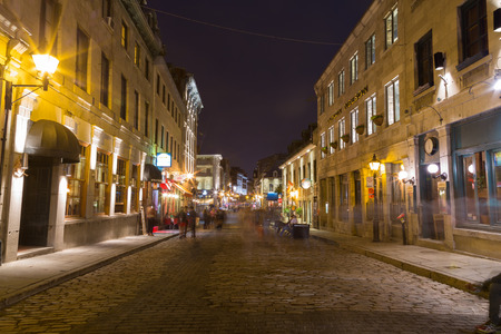 clear path: MONTREAL, CANADA - 17TH MAY 2015: A view along Rue Saint Paul Est in Old Town Montreal at night showing buildings and the blur of people