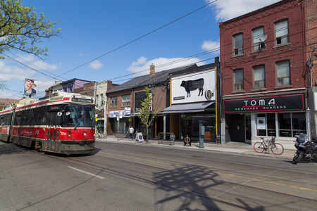 streetcar: TORONTO, CANADA - 19TH MAY 2015: A view along Queen Street in Toronto showing businesses and buildings. People and a TTC Streetcar can be seen.