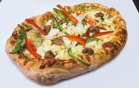 italian sausage: Fresh pizza closeup with italian sausage, peppers, onions, goat cheese and mozzarella toppings