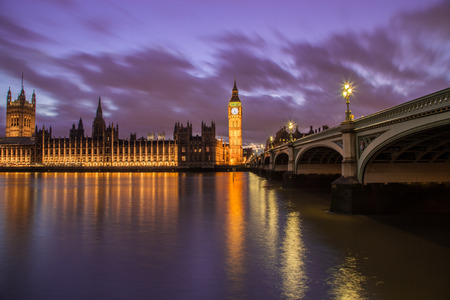 river thames: Houses of Parliament from across the River Thames at dusk. Part of Westminster Bridge can be seen.