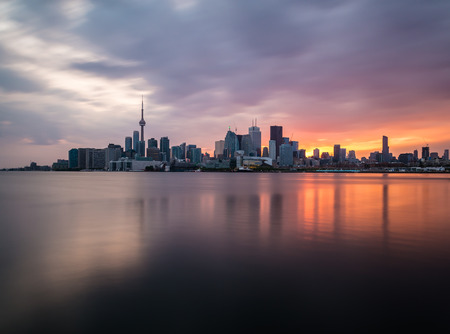 A view of the Toronto Skyline at sunset with reflections in the water. Taken with a long exposure.