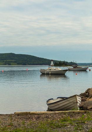 nova scotia: Boats at the waterfront in Baddeck, Nova Scotia during the day. There is space for text.
