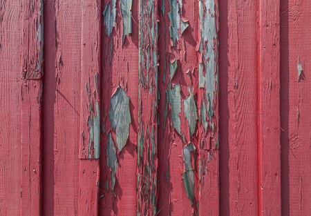 lumpy: A full frame red wood texture with peeling paint and space for text