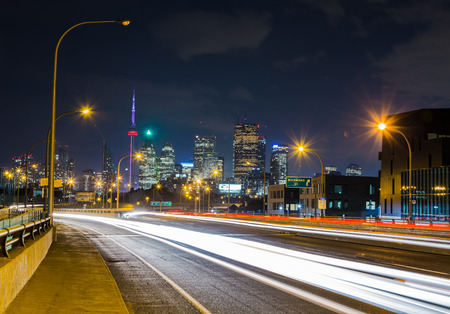 building cn tower: TORONTO, CANADA - 18TH JUNE 2015: Downtown Toronto viewed from the Lake Shore Boulevard East road. The trails of cars can be seen going past.