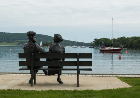 BADDECK, CANADA - 5TH JULY 2015: A statue of a man and a lady at the Baddeck waterfront in Nova Scotia. Boats and a Lighthouse can be seen in the distance.