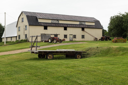 canada agriculture: CAPE BRETON, CANADA - 5TH JULY 2015: The outside of a Barn with lots of Farm equipment outside during an overcast day in the summer