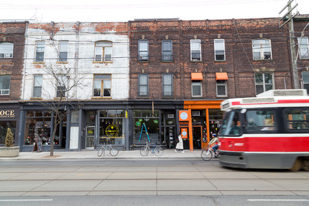 TORONTO, CANADA - 11TH MAY 2015: Buildings along Queen Street West in Toronto showing the design of the buildings. A Streetcar and people can be seen.