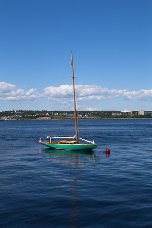 green boat: HALIFAX, CANADA - 3RD JULY 2015: A green boat docked at the Halifax waterfront during the day Editorial