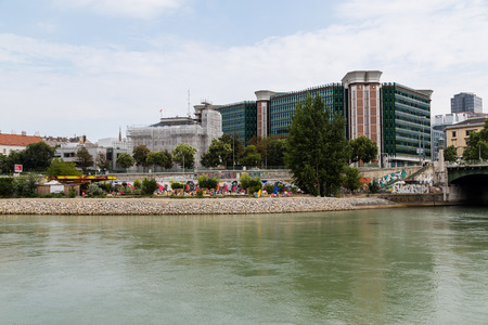 deck chairs: VIENNA, AUSTRIA - 2ND AUGUST 2015: The outside of buildings along the Danube Canal in Vienna during the day. Deck chairs and people can be seen.