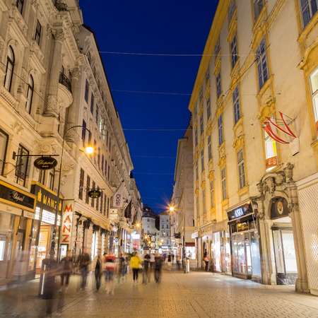 innere: VIENNA, AUSTRIA - 27TH JULY 2015: A view along Kohlmarkt in Vienna at night showing the outside of buildings and the blur of people.