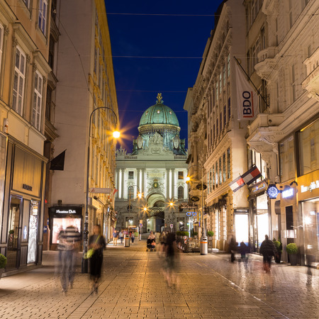 innere: VIENNA, AUSTRIA - 27TH JULY 2015: A view along Kohlmarkt in Vienna at night showing the outside of buildings and the blur of people. Part of the Hofburg can be seen in the distance.