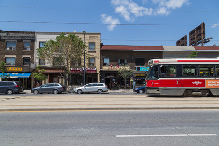 streetcar: TORONTO, CANADA - 2ND JUNE 2015: Buildings along St Clair West in Toronto during the day. A Streetcar can be seen and other vehicles.