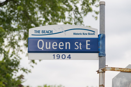toronto: TORONTO, CANADA - 25TH JUNE 2015: A sign for Queen Street East in The Beach district of Toronto
