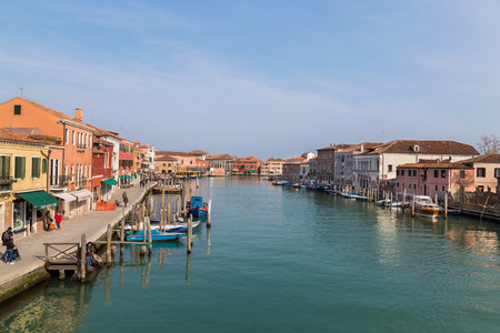 Murano: MURANO, ITALY - 14TH MARCH 2015: Buildings and ports in Murano. People can be seen at the waters edge Editorial