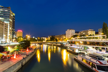 blue hour: VIENNA, AUSTRIA - 21ST AUGUST 2015: A view along the Danube Canal during the blue hour. People, buildings, bars and boats can be seen.